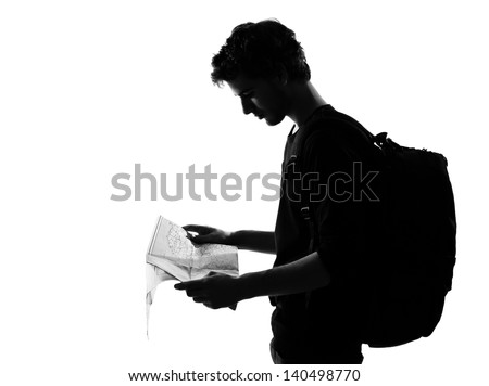young man backpacker reading map silhouette in studio isolated on white background