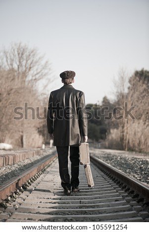 Young man backward with hat and old open suitcase in rail way - stock photo