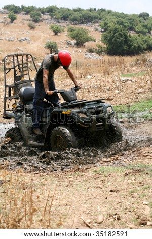 Young man badly stuck in mud with his quadbike - stock photo
