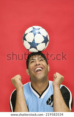 Young man balancing soccer ball on head - stock photo
