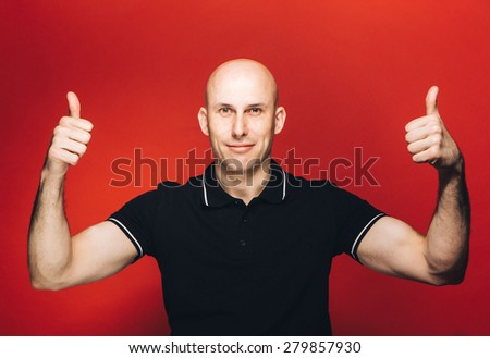 Young man bald portrait on red background thumb up - stock photo