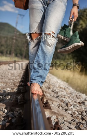 Young man barefoot  legs in ripped jeans close up image