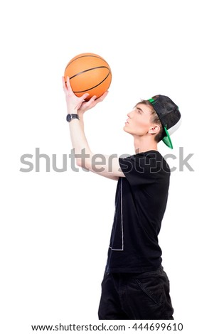 Young man basketball player playing with a ball. Isolated over white.