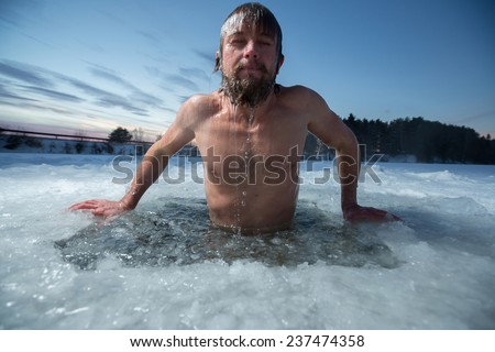 Young man bathing in the ice hole - stock photo