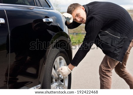 Young man battling to change the tyre on his car leaning his forehead against the side of the vehicle as he struggles to loosen the nuts with a wheel spanner - stock photo