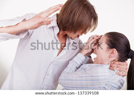 Young man beats his woman. Woman victim of domestic violence and abuse - stock photo