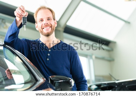 Young man beside a new car in car dealership, obviously he is buying the auto, or making a test drive and holding the keys in hand - stock photo
