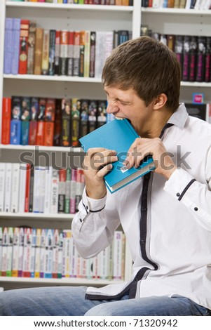 Young man bite a book in the bookshop