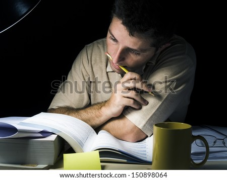 Young Man Biting Pencil Studyng at Night isolated on black background - stock photo