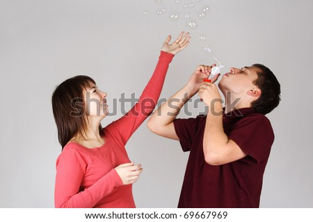 young man blowing out soap bubbles, girl in red shirt smiling and catching it - stock photo