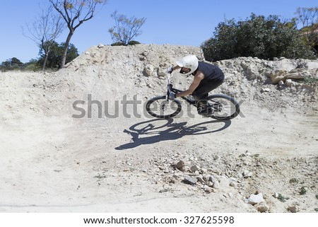 young man BMX biker riding with his bike on a BMX circuit in the mountain - focus on the back - stock photo