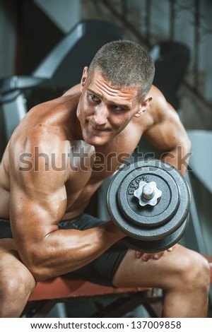 young man bodybuilder doing workout with heavy dumbbell  at gym - stock photo