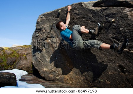 Young man bouldering in the nature environment - stock photo