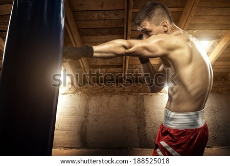 Young man boxing, exercise in the attic - stock photo