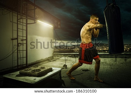 Young man boxing training , on top of the house above the city - stock photo