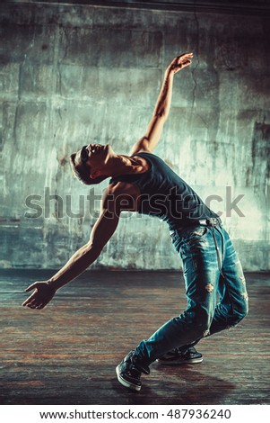 Young man break dancer standing on old wall background