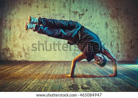 Young man break dancing on wall background. Blue and yellow vibrant colors tint.
