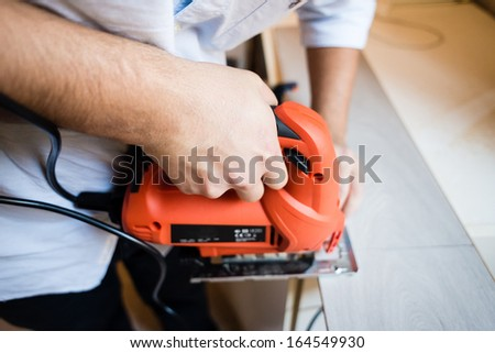 young man bricolage working sawing at home - stock photo