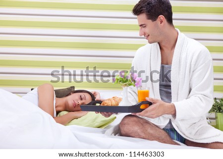 Young man bringing breakfast in bed his sleeping wife