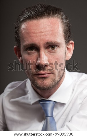 Young man brown hair wearing white shirt and blue tie showing emotions. Isolated on grey background.