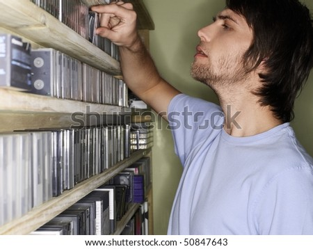Young man browsing music collection, side view. - stock photo