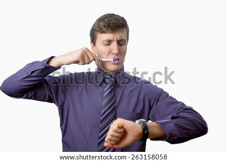 Young man brushing his teeth also looks on at watch on white background