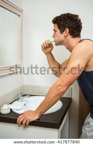 Young man brushing his teeth in front of bathroom mirror
