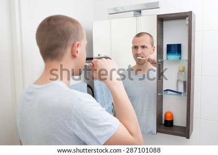 young man brushing teeth and looking at mirror in bathroom - stock photo