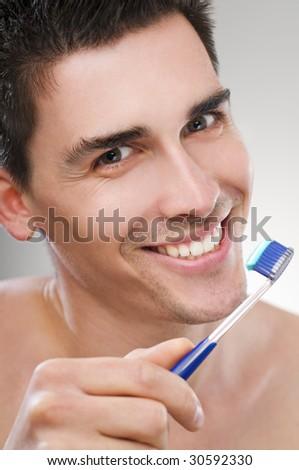 Young man brushing teeth close up shoot - stock photo