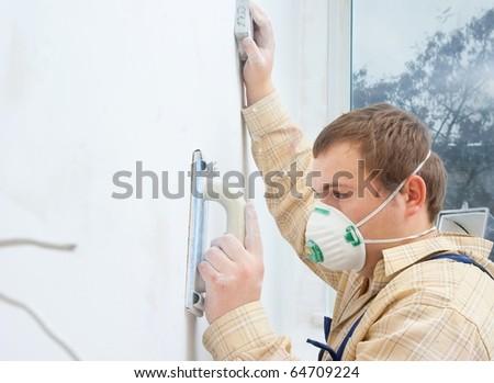 Young man builder polishing the wall - stock photo