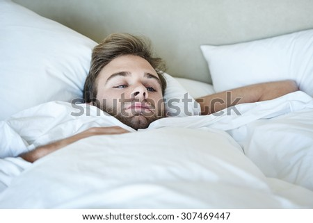 Young man busy looking out his apartment window while lying in his white bedding alone in the morning before work