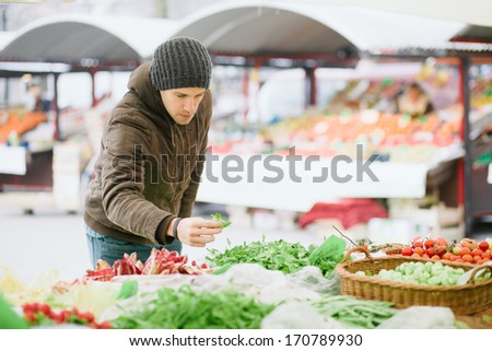Young man buying fresh vegetables at farmer's market - stock photo