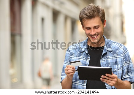 Young man buying online with a credit card and a tablet in the street - stock photo