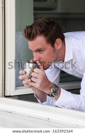 Young man by a window looking out, holding a coffee cup. Wearing a White shirt. - stock photo
