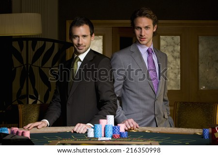 Young man by friend at gambling table, portrait - stock photo