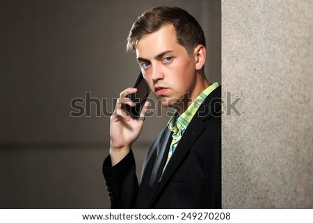 Young man calling on mobile phone at the wall - stock photo