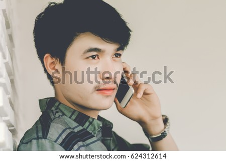 Young man calling with cell telephone while alone in coffee shop during free time.