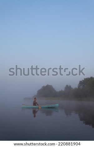 Young man canoeing in Canada at dawn - stock photo