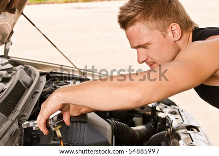 Young man car mechanician repairs engine of car and smiles.