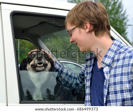 Young man caresses dog (Lapland Reindeer dog, Reindeer Herder, lapinporokoira (Finnish), lapsk vallhund (Swedish) in car.