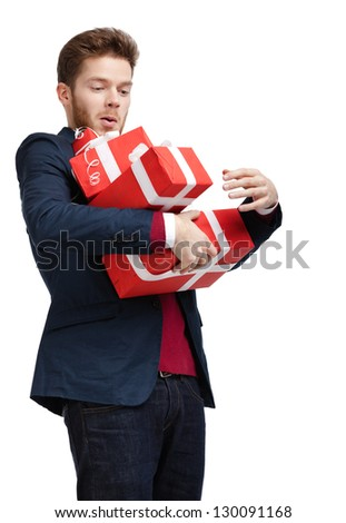 Young man carries a great amount of presents wrapped in red gift paper, isolated on white - stock photo