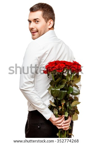 Young man carries flowers isolated on white