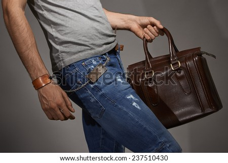 Young man carrying a leather bag against grey background - stock photo