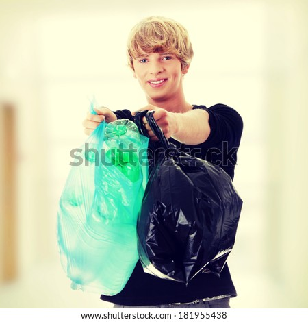 Young man carrying a plastic trash bags full with empty recyclable household material. - stock photo