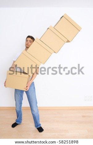 Young man carrying and dropping his stack of moving boxes