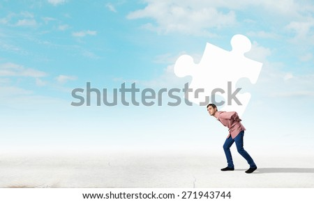 Young man carrying element of jigsaw on his back