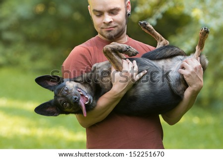 Young man carrying funny dog in his arms - stock photo