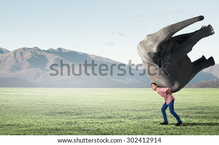 Young man carrying heavy elephant on his back