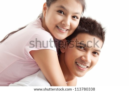 Young man carrying his girlfriend piggyback - stock photo