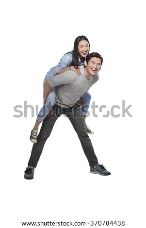Young man carrying his laughing partner isolated over white background